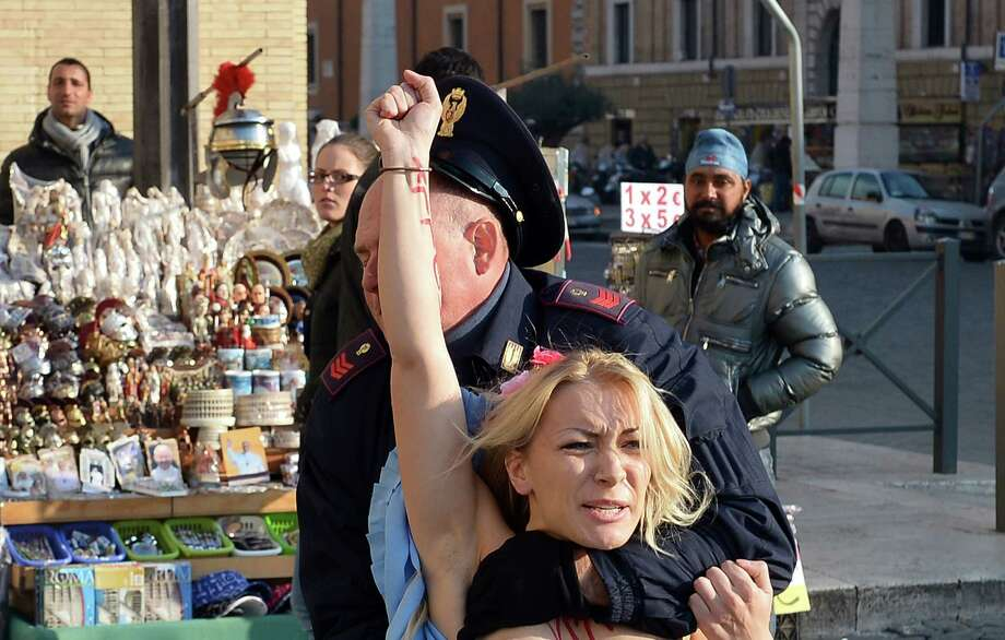 Inna Shevchenko, leader of the Ukrainian feminist protest group Femen runs away from a policeman outside Saint Peter's Square in the Vatican on December 19, 2013. Femen activists have started an international topless marathon to protest against the Catholic church's views on abortion.   AFP PHOTO / GABRIEL BOUYS Photo: GABRIEL BOUYS, Getty Images / 2013 AFP