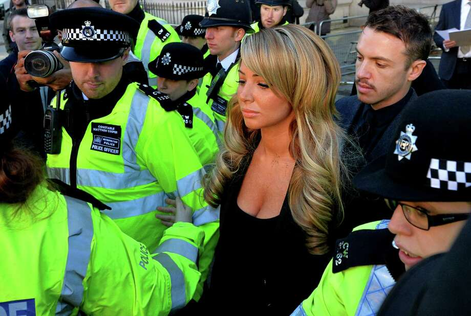 British singer Tulisa Contostavlos (3rd R) leaves Westminister Magistrates Court in London, on December 19, 2013. Contostavlos, 25, denied being concerned with the supply of Class A drugs at Westminster Magistrates Court on Thursday.  She is accused of setting up an £860 deal for 13.9 grams of cocaine to an undercover reporter. AFP PHOTO / BEN STANSALL Photo: BEN STANSALL, Getty Images / 2013 AFP