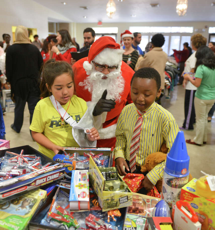 Santa helps Sobeiea (cq) Grohman-Pena (left) and Cherif Mouhamed pick out Christmas gifts during the Bexar County Young Tejano Democrats/Brown Berets toy drive at the House of Prayer Lutheran Church Sunday, Dec. 22, 2013. Photo: Robin Jerstad, For The San Antonio Express-News