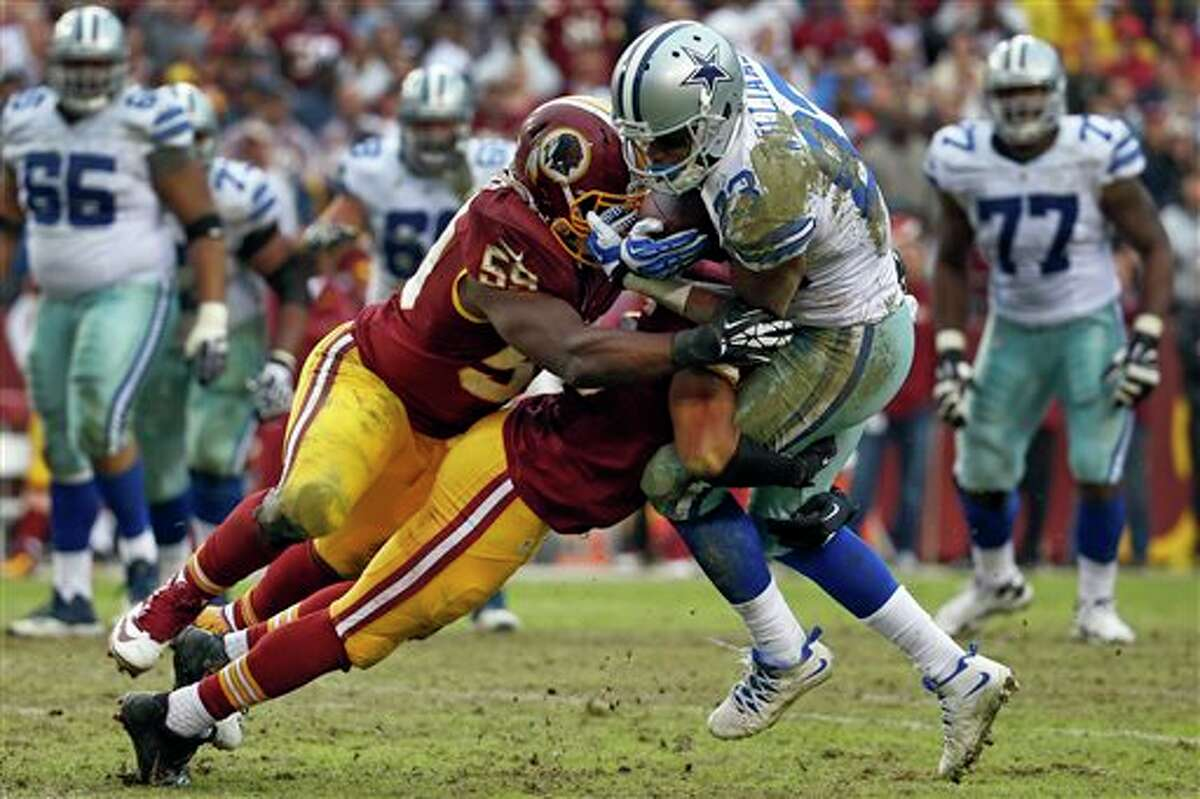 Dallas Cowboys wide receiver Terrance Williams is stopped by Washington Redskins inside linebacker London Fletcher (59) and another defender during the second half of an NFL football game in Landover, Md., Sunday, Dec. 22, 2013.