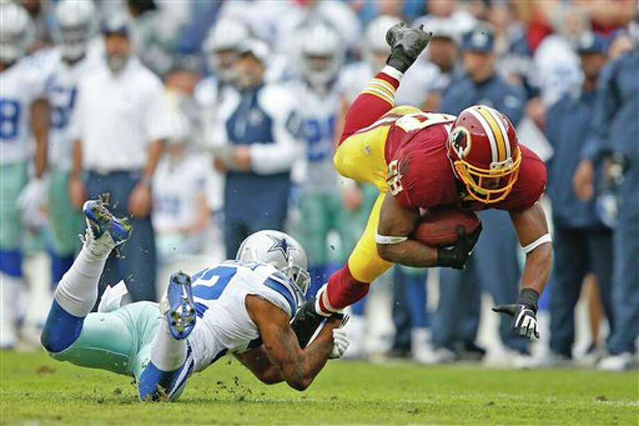 Washington Redskins wide receiver Pierre Garcon is stopped by Dallas Cowboys cornerback Orlando Scandrick during the first half of an NFL football game in Landover, Md., Sunday, Dec. 22, 2013. Photo: Evan Vucci, AP / AP