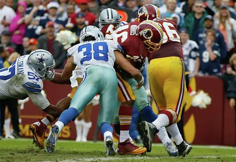 Washington Redskins running back Alfred Morris punches his way into the end zone for a touchdown past Dallas Cowboys strong safety Jeff Heath during the second half of an NFL football game in Landover, Md., Sunday, Dec. 22, 2013. Photo: Evan Vucci, AP / AP