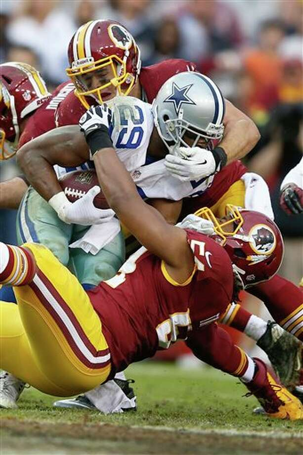 Dallas Cowboys running back DeMarco Murray is stopped by Washington Redskins outside linebacker Ryan Kerrigan, top, and linebacker Darryl Tapp, bottom, during the second half of an NFL football game in Landover, Md., Sunday, Dec. 22, 2013. Photo: Evan Vucci, AP / AP