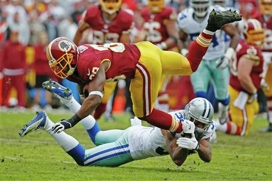 Washington Redskins wide receiver Pierre Garcon is upended by Dallas Cowboys cornerback Orlando Scandrick during the first half of an NFL football game in Landover, Md., Sunday, Dec. 22, 2013. Photo: Alex Brandon, AP / AP