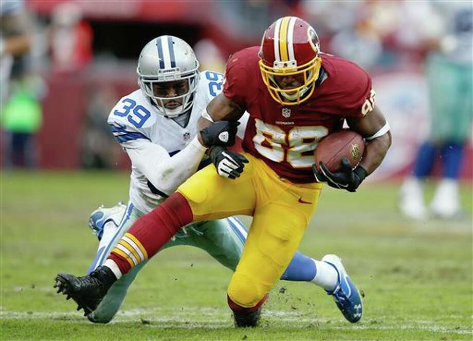 Washington Redskins wide receiver Pierre Garcon is hauled to the turf by Dallas Cowboys cornerback Brandon Carr during the second half of an NFL football game in Landover, Md., Sunday, Dec. 22, 2013. Photo: Evan Vucci, AP / AP