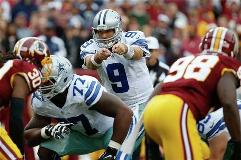 Dallas Cowboys quarterback Tony Romo points down the line during the first half of an NFL football g