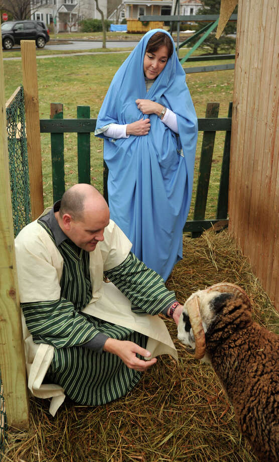 Barbara Wilkov, playing the Virgin Mary, watches as Rev. Mark Montgomery, playing Joseph, feeds one of the sheep on display during the live nativity scene in front of the First Congregational Church of Greenwich in Old Greenwich, Conn., on Sunday, Dec. 22, 2013. Photo: Jason Rearick / Stamford Advocate