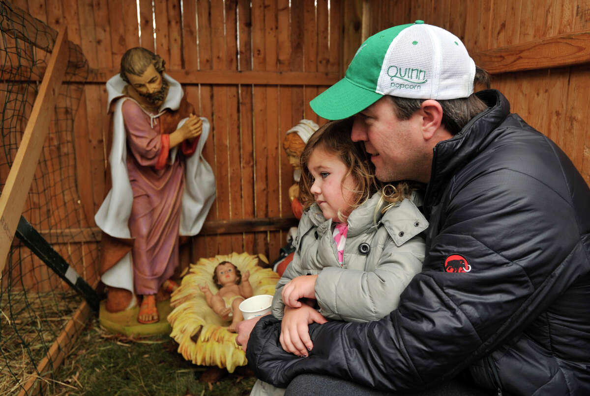 Tim Baker tells his daughter, Reese, about the birth of Jesus during the live nativity scene in front of the First Congregational Church of Greenwich in Old Greenwich, Conn., on Sunday, Dec. 22, 2013.