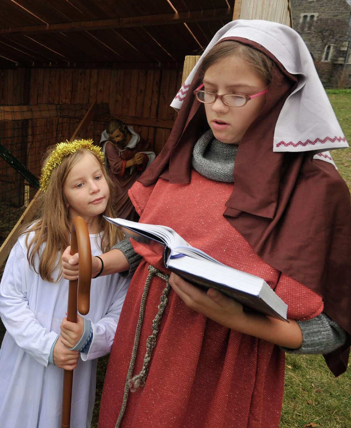 Emma Olmsted, dressed as a shepherd, recites from the Bible as her sister, Lara, dressed as an angel, watches during the live nativity scene in front of the First Congregational Church of Greenwich in Old Greenwich, Conn., on Sunday, Dec. 22, 2013.
