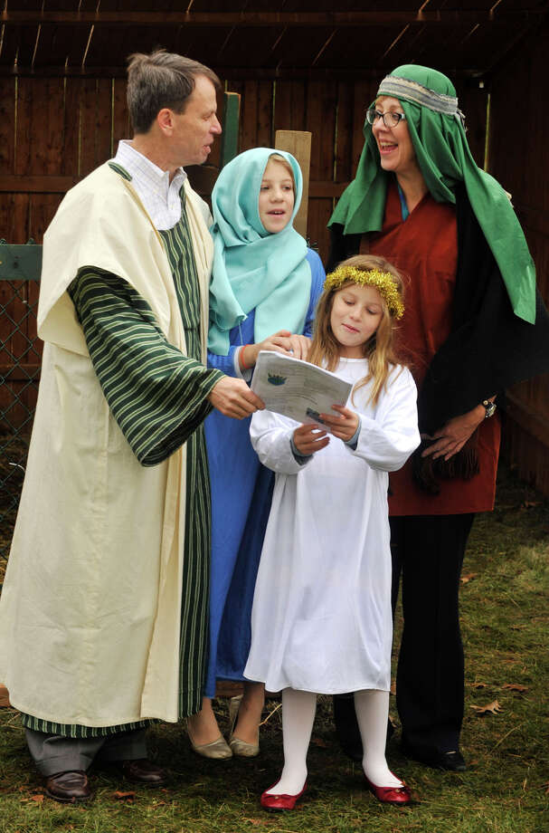 Paul and Cara Olmsted sing Christmas carols with their daughters, Jennie, center top, and Lara during the live nativity scene in front of the First Congregational Church of Greenwich in Old Greenwich, Conn., on Sunday, Dec. 22, 2013. Photo: Jason Rearick / Stamford Advocate