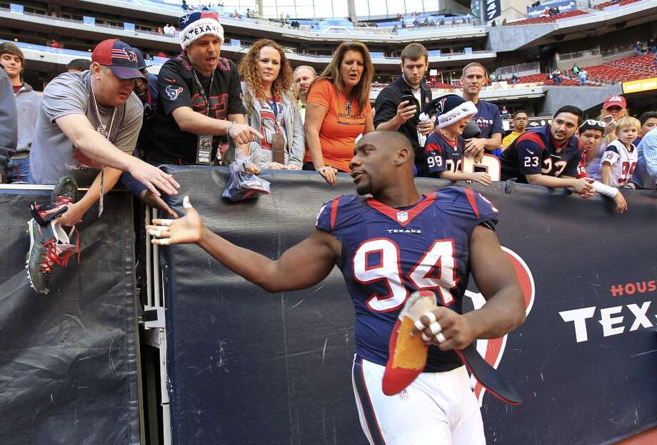 Defensive end Antonio Smith shakes a fan's hand after giving him his shoes after the loss. Photo: Karen Warren, Houston Chronicle