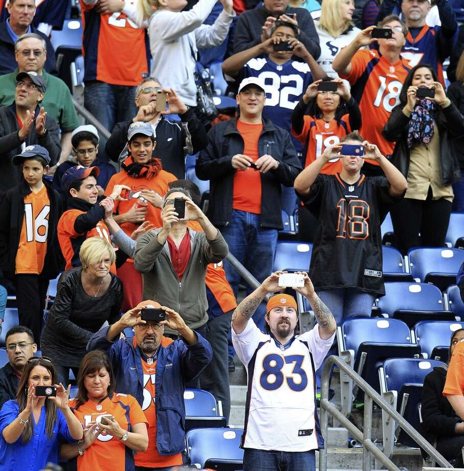 Broncos fans take photos from the stands after Denver quarterback Peyton Manning broke the NFL record for touchdown passes in a season during the fourth quarter. Photo: Karen Warren, Houston Chronicle