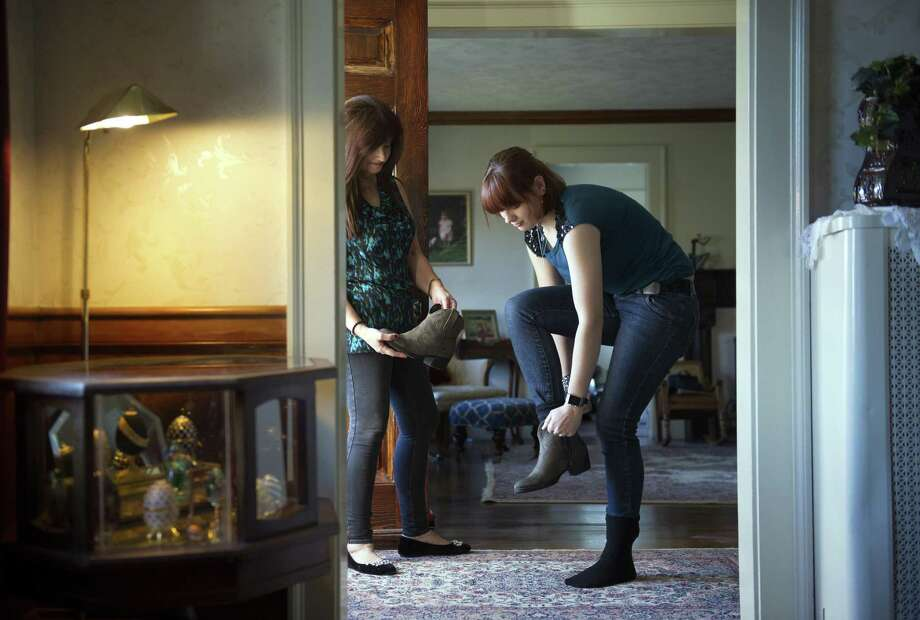 Alexa Portney tries on boots that her mother, Marilyn Santiesteban (left), bargained for in Newton, Mass. Photo: Gretchen Ertl, New York Times / NYTNS