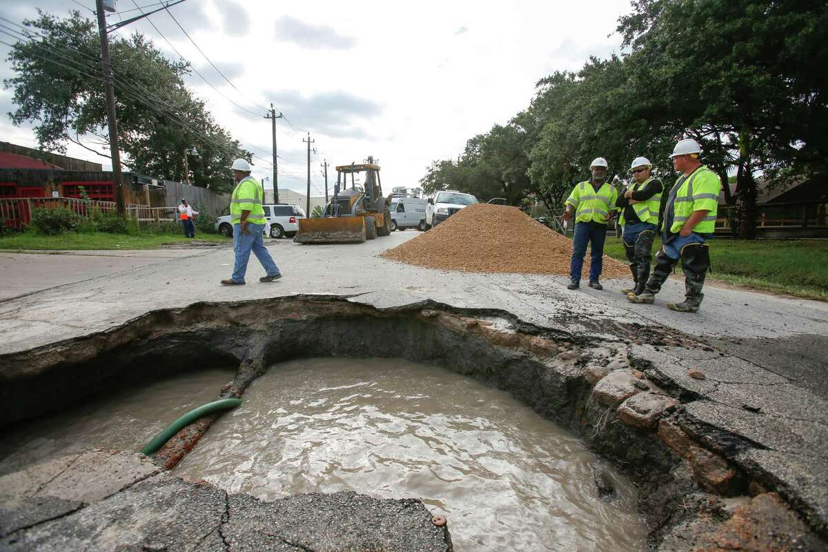 Workers pump water out of a large sinkhole that was caused by a water main break that opened up and swallowed a car earlier on Sept. 23, 2013, at Fairdale and Fountain View.