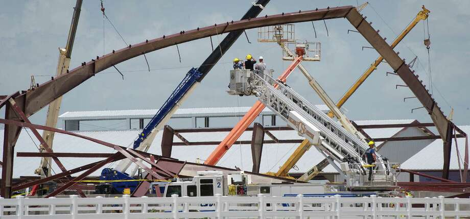 FILE - This June 22, 2013 file photo shows College Station firefighters surveying the damage following the collapse of a building frame of the Texas A&M University equestrian center near College Station, Texas. Safety regulators have cited two construction companies after the framing for a barn collapsed at the $80 million Texas A&M University equestrian complex. (AP Photo/Bryan College Station Eagle, Stuart Villanueva) Photo: Stuart Villanueva, MBR / BRYAN COLLEGE STATION EAGLE