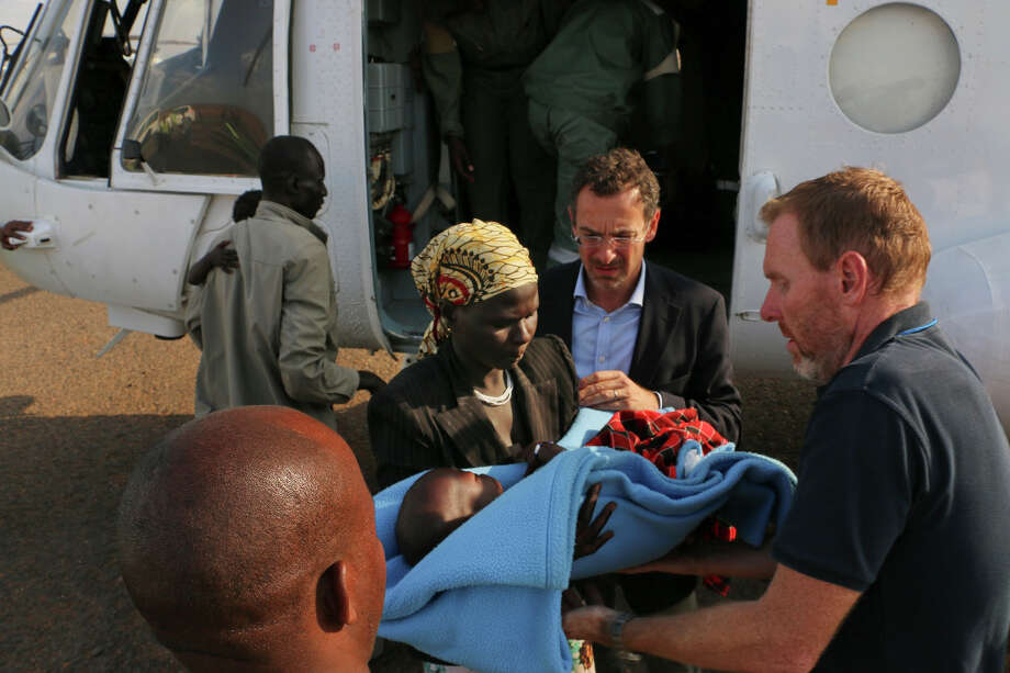 In this photo released by the United Nations Mission in South Sudan (UNMISS), wounded civilians from Bor, the capital of Jonglei state and said to be the scene of fierce clashes between government troops and rebels, are assisted after being transported by U.N. helicopter to Juba, South Sudan, Sunday, Dec. 22, 2013. South Sudan's central government lost control of the capital of a key oil-producing state on Sunday, the military said, as renegade forces loyal to a former deputy president seized more territory in fighting that has raised fears of full-blown civil war in the world's newest country. (AP Photo/UNMISS) Photo: HOEP / UNMISS