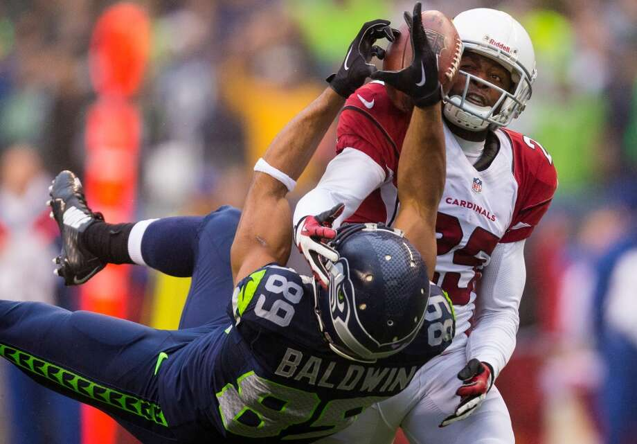 Seattle Seahawk Doug Baldwin, bottom, fails to make a long-range catch after a blow from Arizona Cardinal Jerraud Powers, right, during the second half of a game Sunday, Dec. 22, 2013, at CenturyLink Field in Seattle. The Cardinals beat the Seahawks 17-10. (Jordan Stead, seattlepi.com) Photo: JORDAN STEAD, SEATTLEPI.COM