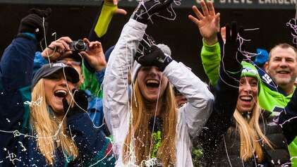 Seahawks fans shield themselves against a spray of Silly String during the first half of a game Sunday, Dec. 22, 2013, at CenturyLink Field in Seattle. The score was 3-3 at the half. (Jordan Stead, seattlepi.com)
