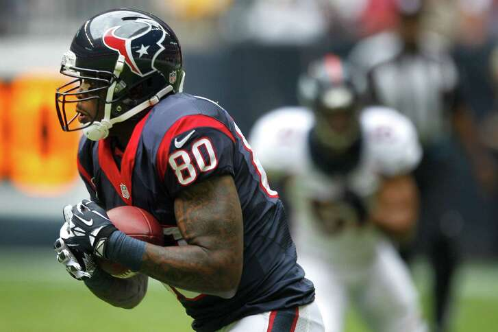 Texans wide receiver Andre Johnson hauls in a 33-yard reception in the first quarter for his 100th catch of the season. He ended Sunday's game with 103 receptions to tie an NFL record with his fifth 100-catch season.
