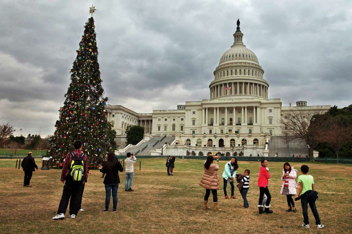Under rolling clouds, tourists remove their jackets as they visit the U.S. Capitol Christmas tree in Washington, Sunday, Dec. 22, 2013. Unseasonably warm temperatures in the low 70's are expected Sunday in the Washington region, with rain likely. Temperatures are expected to dip down to the 30's and 40's later in the week, according to the National Weather Service. (AP Photo/Jacquelyn Martin) ORG XMIT: DCJM101