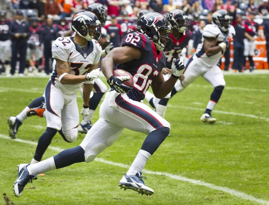 Texans wide receiver Keshawn Martin runs past Broncos defensive back Tony Carter for a 51-yard punt return. Photo: Brett Coomer, Houston Chronicle