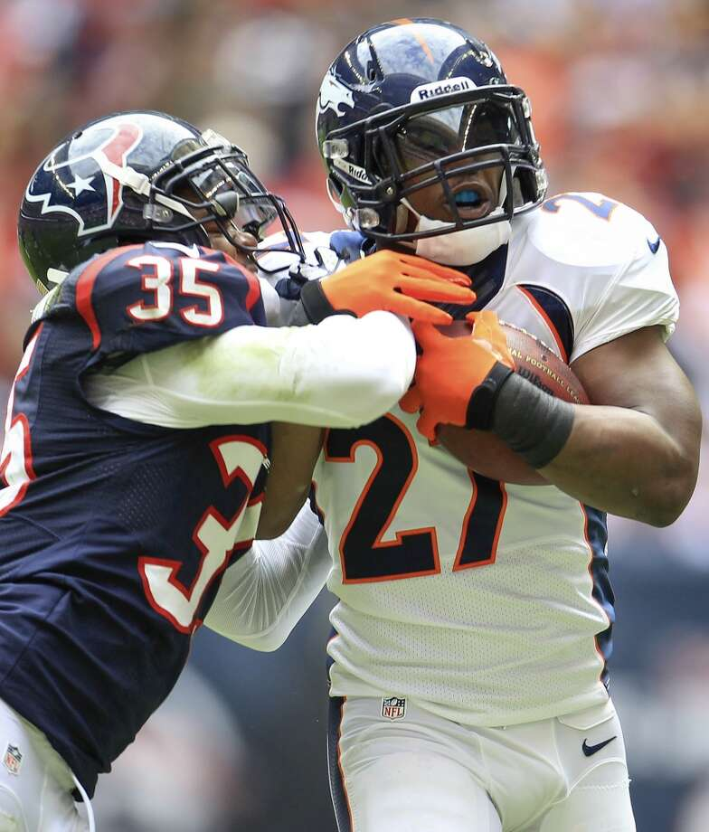 Broncos running back Knowshon Moreno is tackled by Texans safety Eddie Pleasant. Photo: Karen Warren, Houston Chronicle