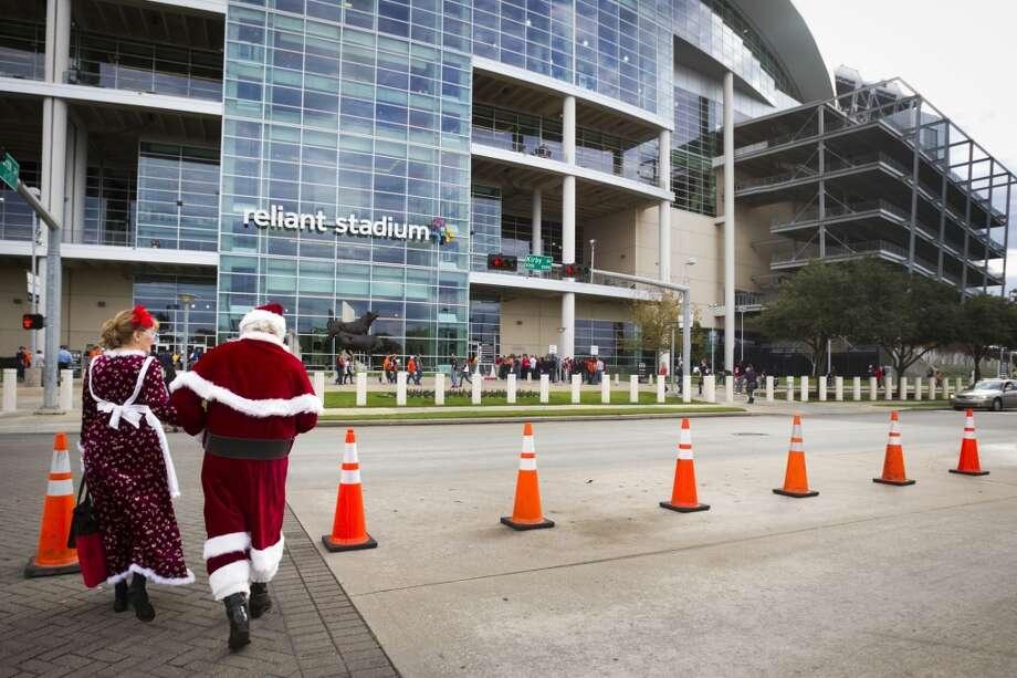 Carolyn and John Hancock walk across the street to Reliant Stadium as Santa and Mrs. Claus. Photo: Brett Coomer, Houston Chronicle