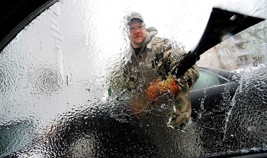Charles Winslow clears ice off of his car in Lewiston, Maine, amid ice build-up on tree limbs that brought down power lines in the region, leaving thousands of homes and businesses in Vermont and Maine without electricity. Photo: Amber Waterman / Lewiston Sun Journal / The Sun-Journal