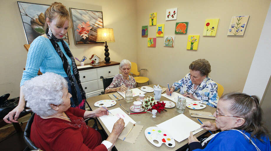 """Gina Reese (standing), art teacher at the Franklin Park at Stone Oak assisted living community, conducts a painting class with residents Lucy Berban (from left), Faye Sandlin, Micheline """"Mickey"""" Ohlenforst and Bernice """"Bee"""" Buchanan. Photo: Marvin Pfeiffer / San Antonio Express-News / Express-News 2013"""