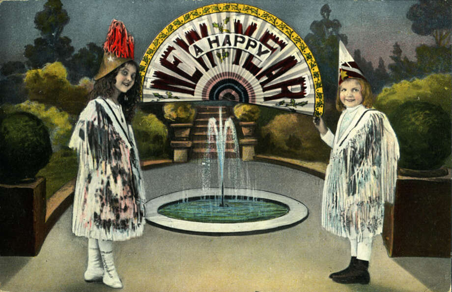 "A strange holiday New Year's greeting with two costumed girls standing in front of a fountain holding an unfurled fan that reads ""A Happy New Year,"" circa 1920. Photo: Transcendental Graphics, Getty Images / Archive Photos"