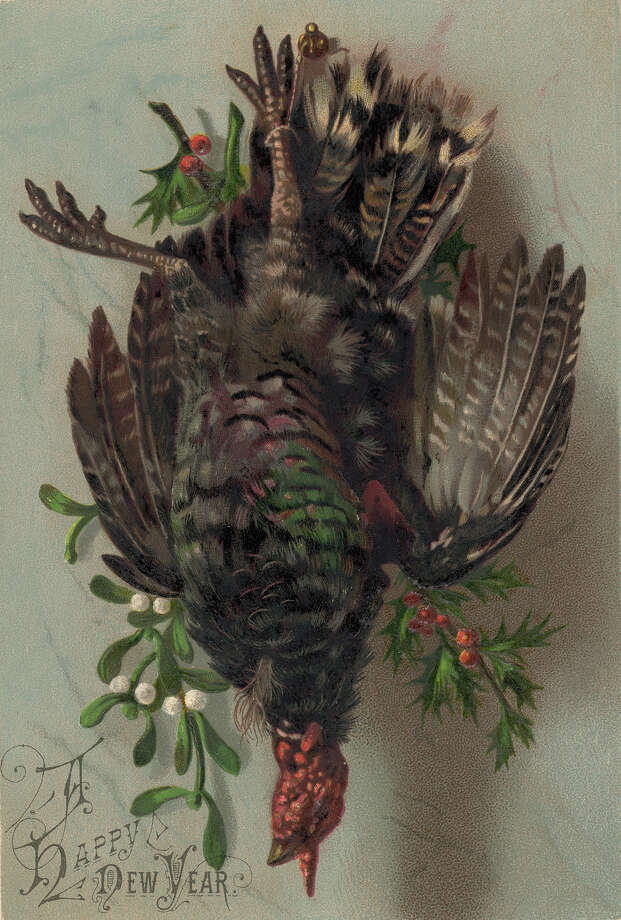 "A ""Happy New Year"" postcard from about 1920 features a turkey hanging on the wall by a nail. Photo: Mansell, Getty Images / Time & Life Pictures"