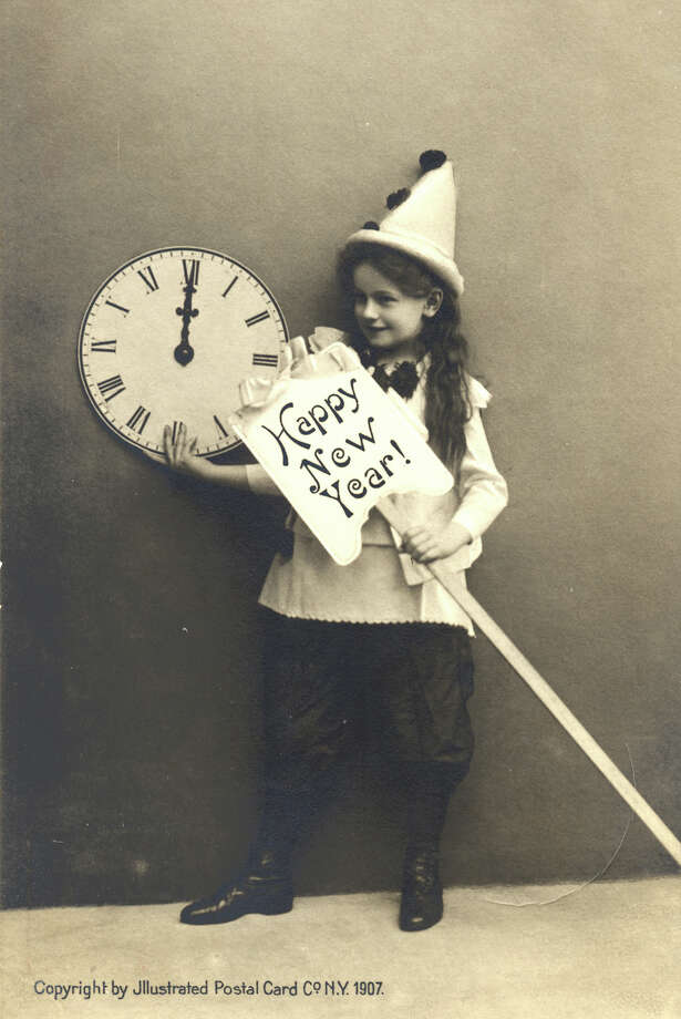 "A young girl dressed as a harlequin holds a clock showing midnight and a sign on a stick which reads ""Happy New Year!"" in a holiday card printed by the Illustrated Postal Car Co., New York, 1907. Photo: Vintage Images, Getty Images / 2006 Getty Images"