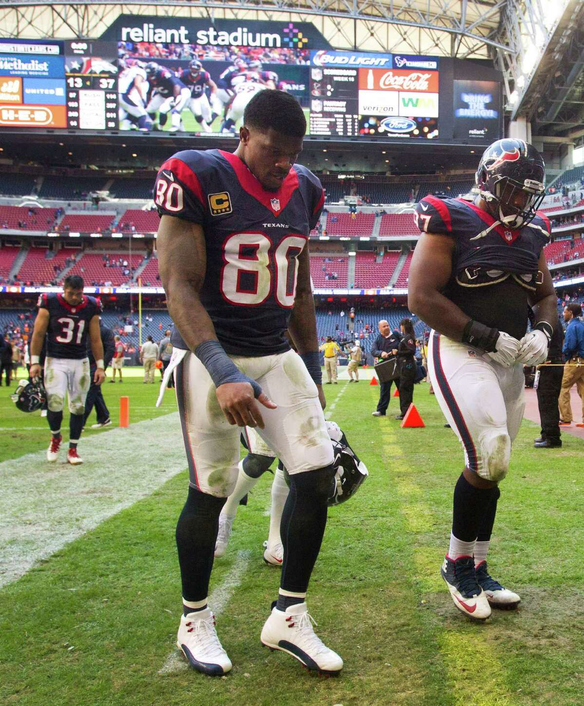 Texans Andre Johnson (80) and Terrell McClain (97) leave the field after falling to Denver 37-13 on Sunday, their 13th consecutive loss and seventh straight at Reliant Stadium. Their last win, which came at home, was Sept. 15, two days after the Astros' final win.