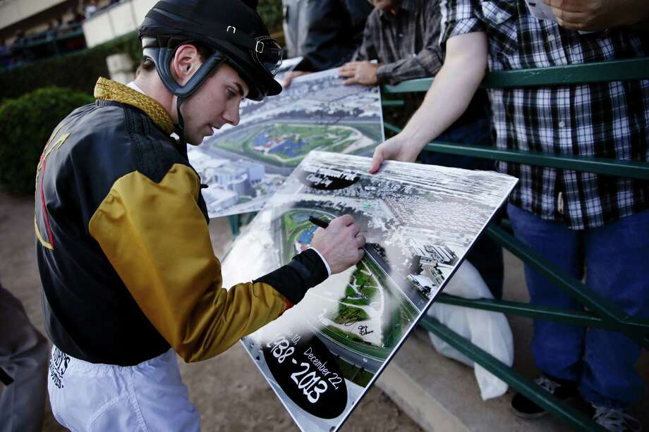 Jockey Joseph Talamo signs posters commemorating the final day of racing at Hollywood Park. The track in Inglewood, Calif., which hosted the first Breeders' Cup in 1984, is closing after 75 years. The site will become a residential and retail complex. Photo: Jae C. Hong, STF / AP