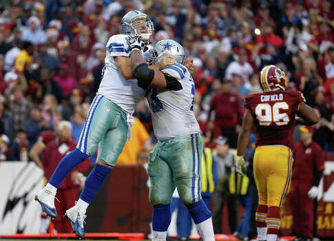 Dallas Cowboys quarterback Tony Romo, left, is hugged by guard Mackenzy Bernadeau as Washington Redskins nose tackle Barry Cofield, right, walks off the field after Romo threw the game tying touchdown pass late in the fourth quarter of an NFL football game in Landover, Md., Sunday, Dec. 22, 2013. The Cowboys defeated the Redskins 24-23. Photo: Alex Brandon, Associated Press / AP