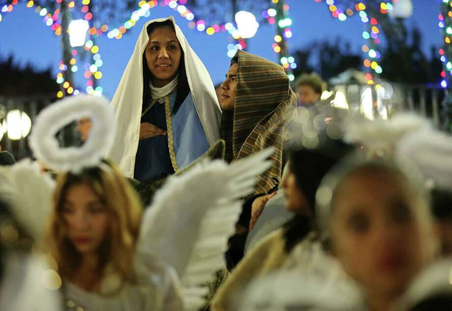 Itzel Esquivel, 18, as Mary (left) and Jacob Holguin, 17, as Joseph wait for the start of La Gran Posada Sunday Dec. 22, 2013 in Milam Park. Photo: San Antonio Express-News / © 2013 San Antonio Express-News