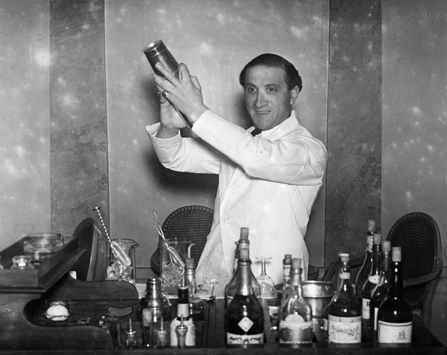 A barman on duty at the cocktail bar of Hector's Devonshire Restaurant in London on New Year's Eve, Dec. 31, 1930, is seen preparing a cocktail, shaken not stirred. Photo: Sasha, Getty Images / Hulton Archive