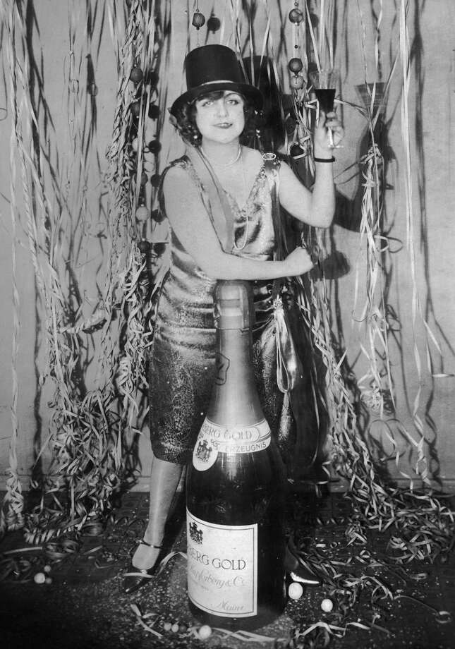 A woman at a New Year's Eve party in Germany leans on an oversized bottle of champagne while making a toast, circa 1925. Photo: Hulton Archive, Getty Images / Archive Photos