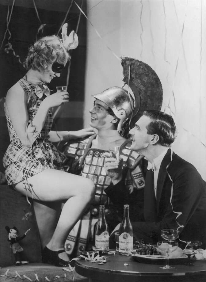 A woman in a mask and plaid costume smiles as she holds a drink, one hand on the shoulder of a smiling man dressed as a Roman centurian while a second man in a suit sits next to them at a New Year's Eve costume ball, circa 1930. Photo: Mansell, Getty Images / Time & Life Pictures