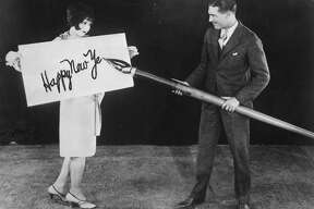 circa 1925: American actress Clara Bow (1905 - 1965) holds up a large card while actor Larry Gray inscribes a New Year's greeting with a giant pen.