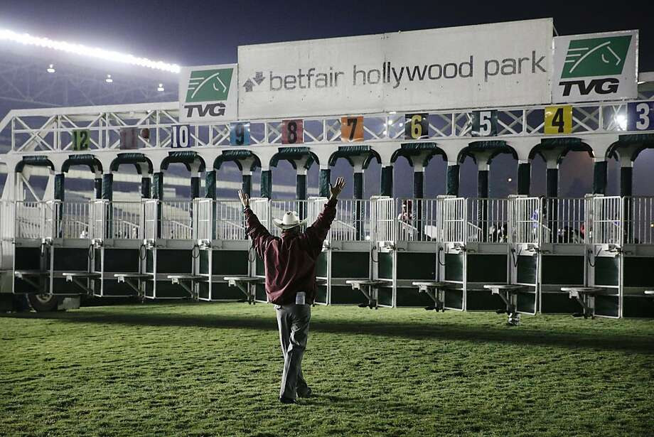 A starter signals while standing in front of the gate before the start of the final race at Betfair Hollywood Park on Sunday, Dec. 22, 2013, in Inglewood, Calif. The track closed for good after the day's 11 horse races, ending 75 years of racing that featured such thoroughbred stars as Seabiscuit, Triple Crown winners Citation, Seattle Slew and Affirmed, and Zenyatta. The first Breeders' Cup in 1984 was run here. The track will be turned into a residential and retail development starting next year. (AP Photo/Jae C. Hong) Photo: Jae C. Hong, Associated Press