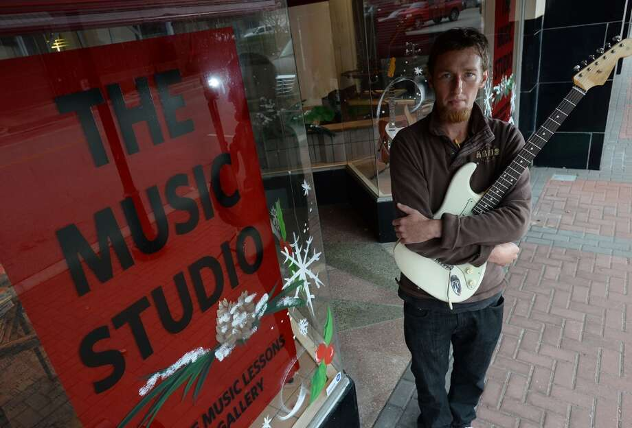 Moving his business downtown, Chris Jetton is the owner of The Music Studio where patrons can learn to play a variety of music and artist can display their work. Photo taken Wednesday, December 11, 2013 Guiseppe Barranco/@spotnewsshooter