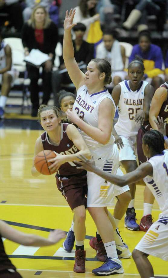 Lauryn Kobiela of Colgate, left, looks for an open teammate after being stopped in the lane by Megan Craig of UAlbany during the UAlbany and Colgate women's basketball game on Sunday, Dec. 22, 2013 in Albany, NY.   (Paul Buckowski / Times Union) Photo: PAUL BUCKOWSKI / 00025117A