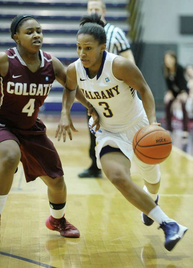 Mariah Jones of Colgate, left, tries to stop Margarita Rosario, right, of UAlbany as she drives towards the basket during the UAlbany and Colgate women's basketball game on Sunday, Dec. 22, 2013 in Albany, NY.   (Paul Buckowski / Times Union) Photo: PAUL BUCKOWSKI / 00025117A