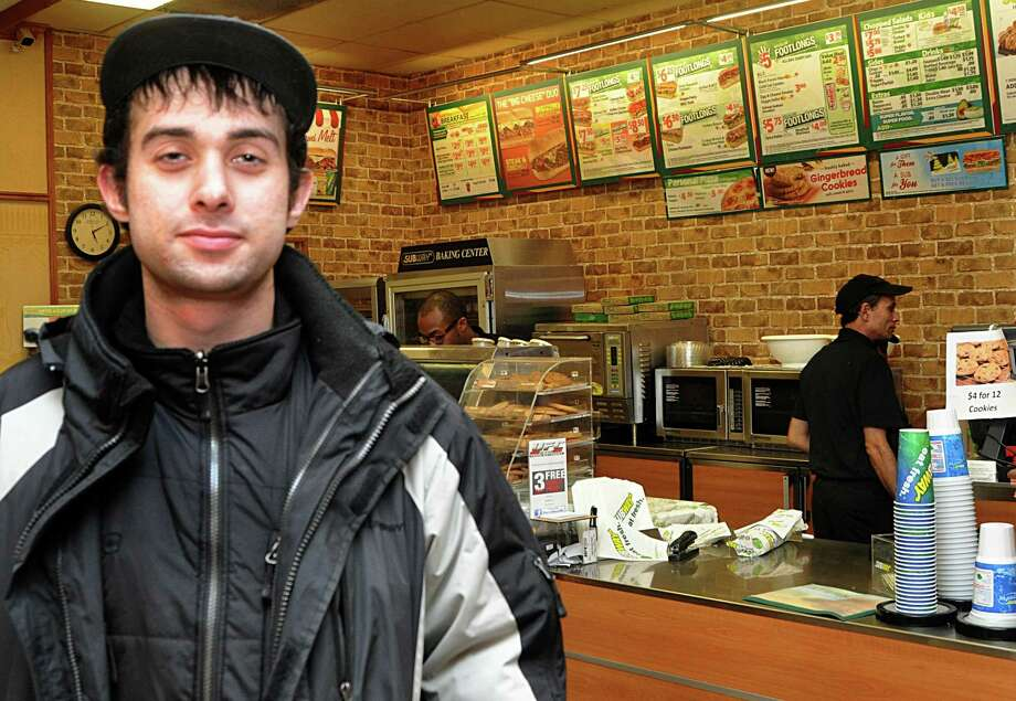 Shahzad Khan, in his sister's Subway sandwich shop, is one of four people being credited by officials with helping children safely exit a school bus that stalled on railroad tracks last week as a train came within 10 feet of striking it. Photo: Nancy Guenther Chapman / Norwalk Citizen contributed