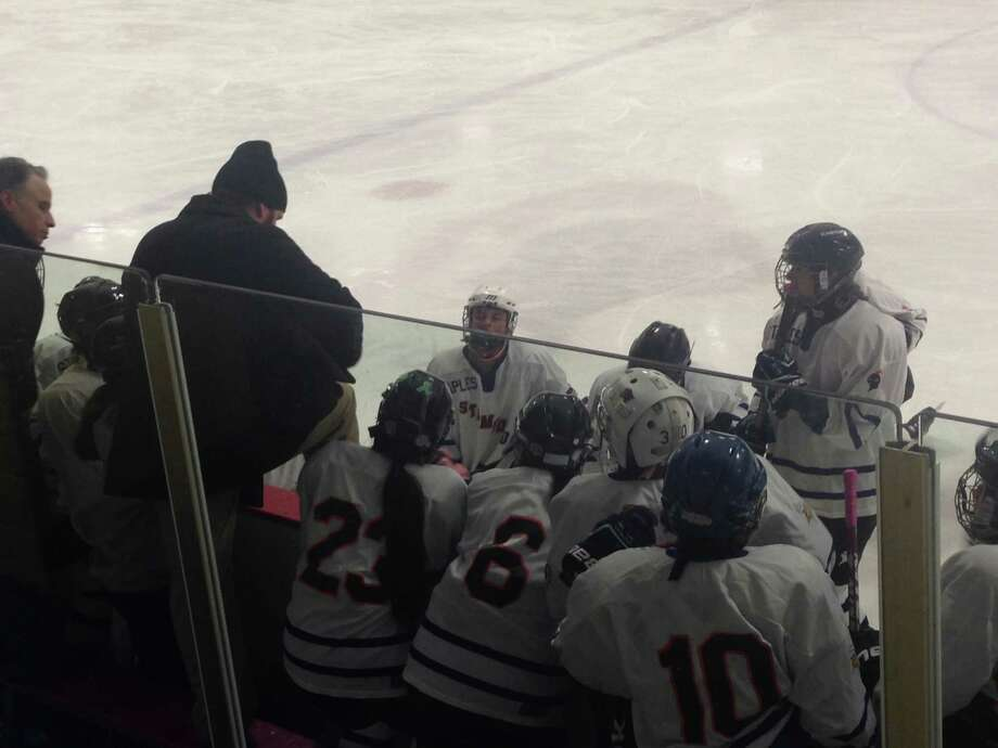 Stamford/Westhill/Staples girls ice hockey coach Eli Williams, center, talks to his team during 8-6 defeat to West Haven Dec. 20. Photo: Ryan Lacey / Westport News Contributed