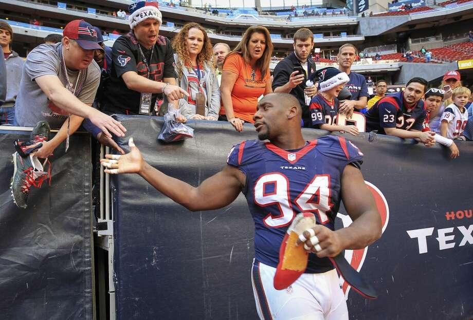 Texans defensive end Antonio Smith gives his shoe to a fan. Photo: Karen Warren, Houston Chronicle