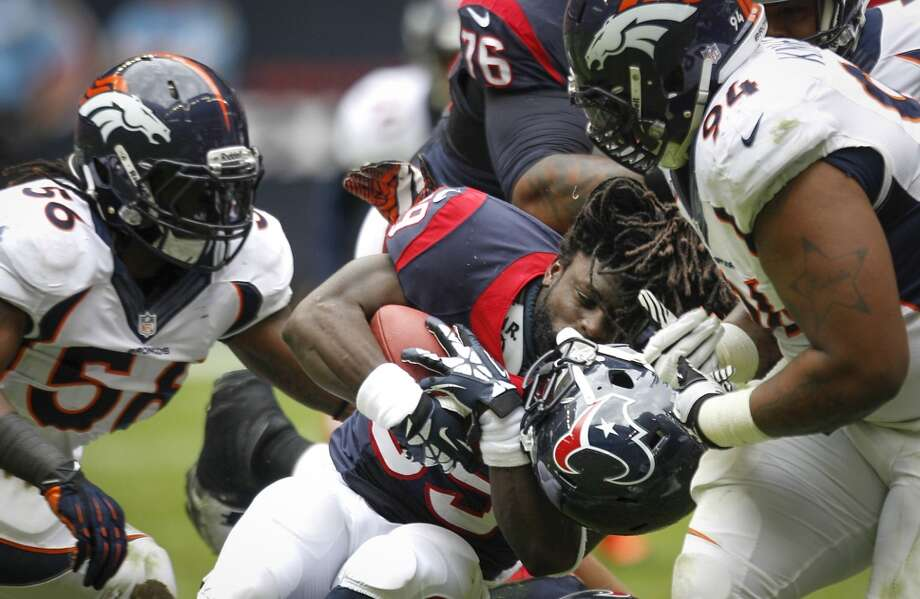 Texans running back Deji Karim (39) has his helmet ripped off by Broncos defensive tackle Terrance Knighton. Photo: Brett Coomer, Houston Chronicle