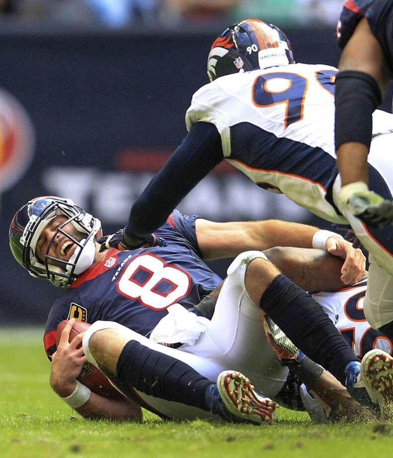 Texans quarterback Matt Schaub reacts after being sacked by Broncos defensive end Shaun Phillips. Photo: Karen Warren, Houston Chronicle