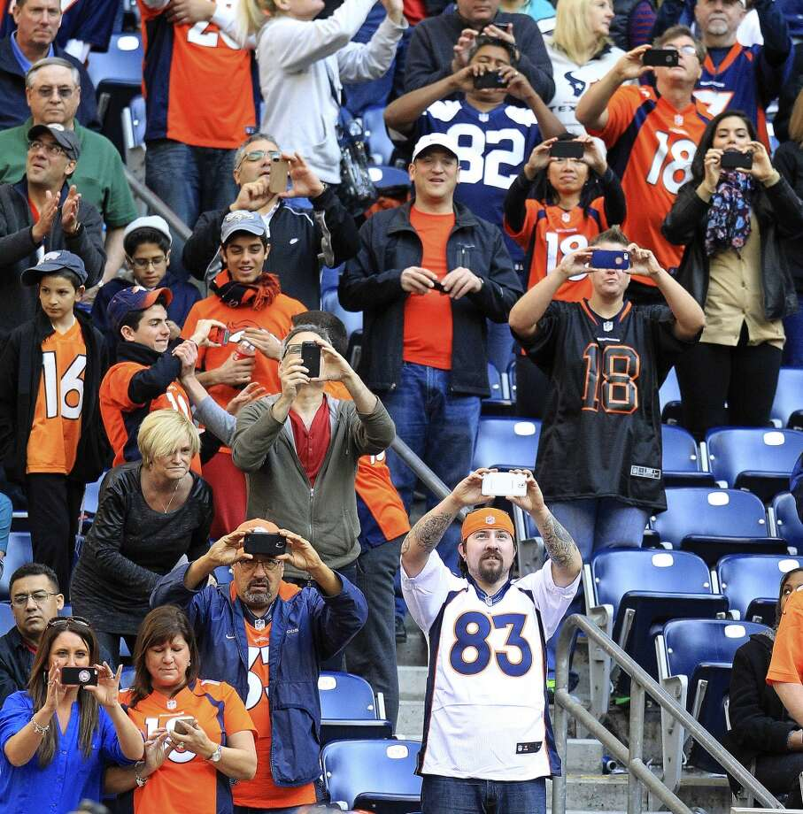 Broncos fans take photos from the stands after quarterback Peyton Manning broke the NFL record for touchdown passes in a season. Photo: Karen Warren, Houston Chronicle